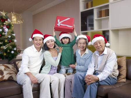 Home portrait of an Asian family with Christmas hats and gifts