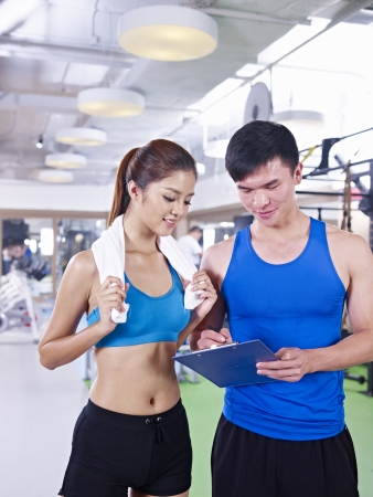 young woman talking to her trainer about her training plan  photo