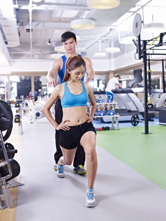 instructing: young woman doing aerobics in gym, guided by trainer  Stock Photo