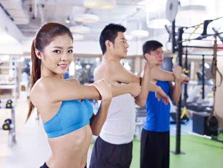 group of people doing aerobics in gym; shallow depth of field, focus on the girl