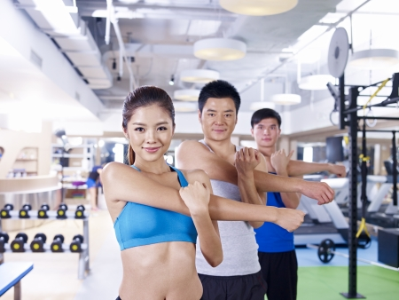 vigorously: group of people doing aerobics in gym; shallow depth of field, focus on the girl