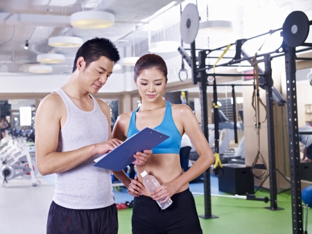 young man and woman discussing workout plan in fitness center
