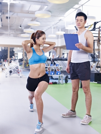 instructing: young woman working out in gym with partner trainer