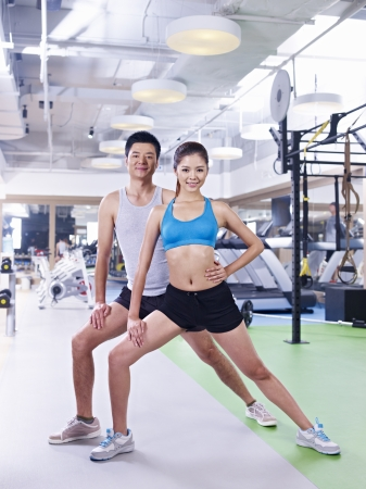 korean man: young asian man and woman working out together in gym