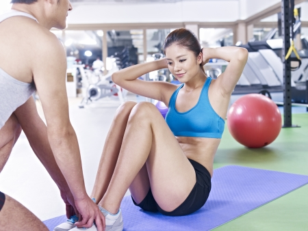 situps: young woman doing sit-ups with help from her partner