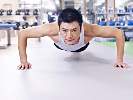 man doing push-ups on gym floor  photo