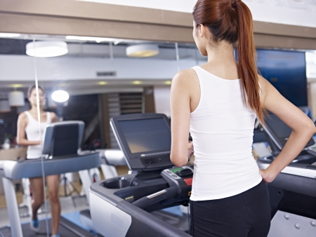 rear view of a young woman running on treadmill  photo