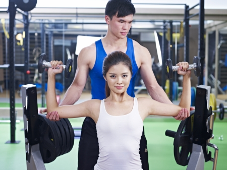 young woman doing body building exercise with help from trainer  photo