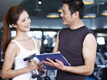 instructor: young couple talking during workout in fitness center