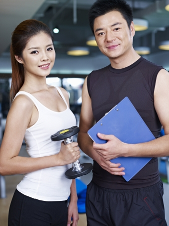 portrait of young man and woman in fitness center  photo