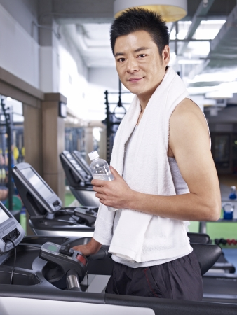 man taking a break while exercising on treadmill  photo