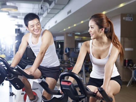 people   lifestyle: young man and woman talking while exercising on bicycle in fitness center