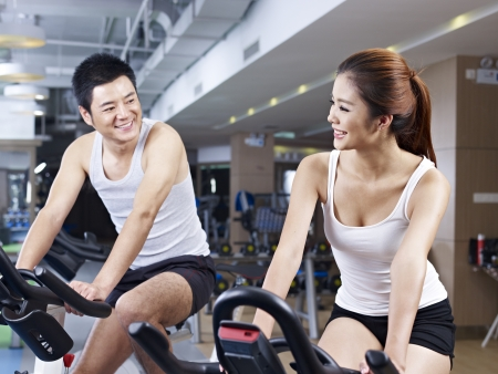 man exercise: young man and woman talking while exercising on bicycle in fitness center