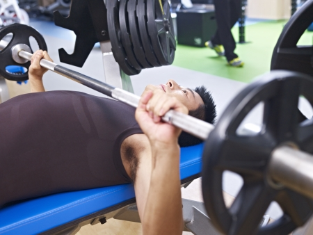conquer adversity: man doing bench press in gym  Stock Photo