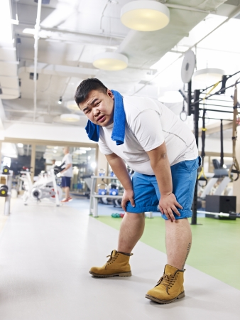 exhausted overweight young man in fitness center  photo