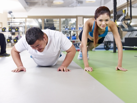 an overweight young man doing push-ups together with a young lady