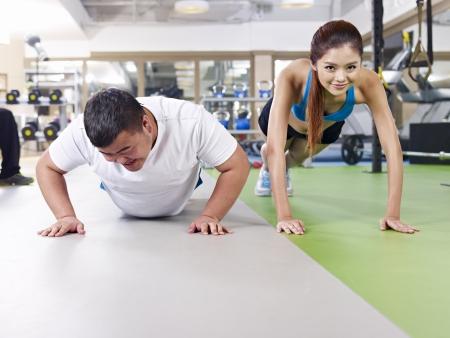 hombres haciendo ejercicio: un hombre con sobrepeso joven haciendo flexiones junto a una joven