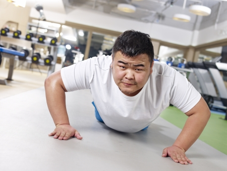 an overweight young man doing push-ups with sweating face  photo