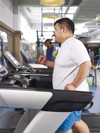 an overweight young man running on treadmill in fitness center