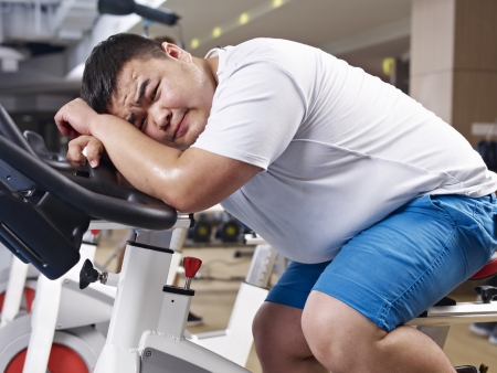 tired: an overweight young man exhausted with exercising in fitness center