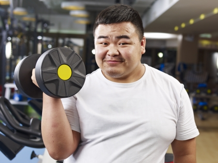 man working out: an overweight young man holding a dumbbell in fitness center