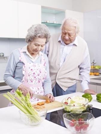 persona de la tercera edad: Pares asi�ticos mayores que preparan la comida juntos en la cocina Foto de archivo