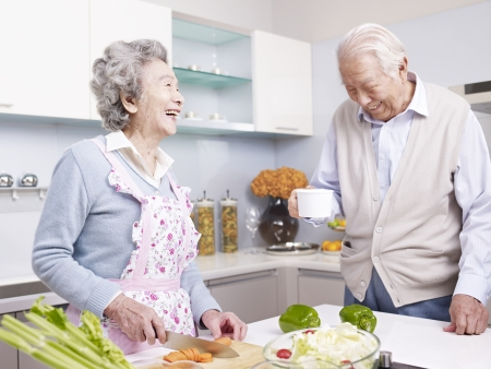 senior asian couple talking and laughing in kitchen