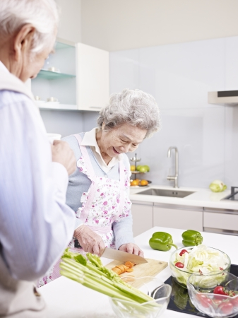 senior asian couple preparing meal together in kitchen  photo