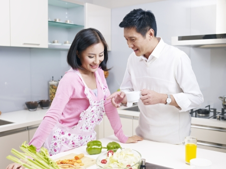 esposas: joven pareja asian hablando en la cocina