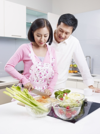young asian couple preparing meal together in kitchen