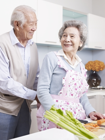 love couple: senior man tying apron for his wife