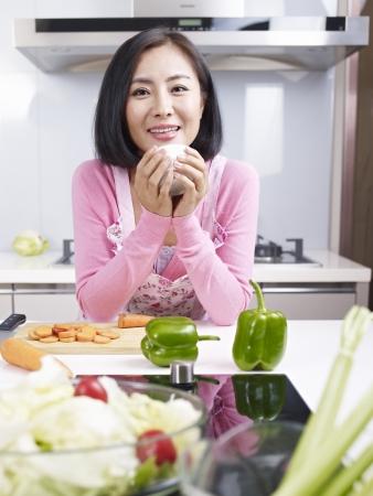 asian woman taking a break in kitchen  photo