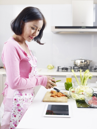 asian housewife looking at tablet computer while preparing meal  photo
