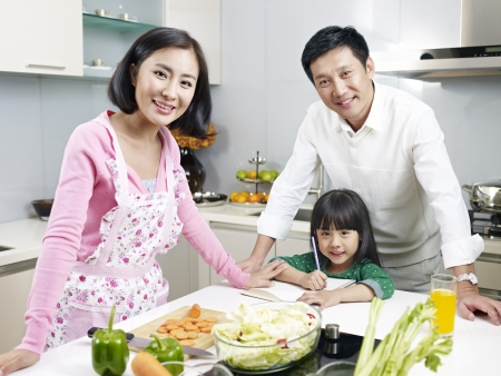 supportive: asian family of three smiling in kitchen