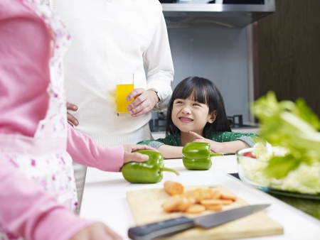 children talking: little asian girl talking to parents and smiling in kitchen  Stock Photo