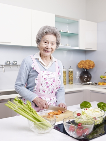 senior asian woman cutting carrot to make salad in kitchen  photo
