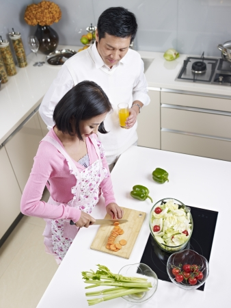 asian couple preparing meal together in kitchen  photo