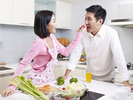romantic asian couple preparing meal in kitchen  photo