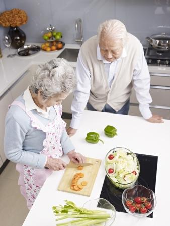 ハイアングルビュー: 食事を準備しながら話している年配のカップルの高角度のビュー