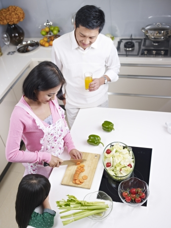 preparing food: high angle view of an asian family preparing meal in kitchen