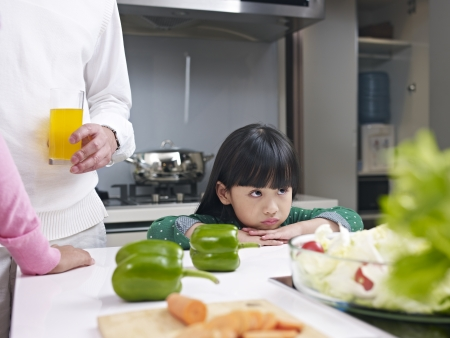 little girl appears unhappy in kitchen  photo