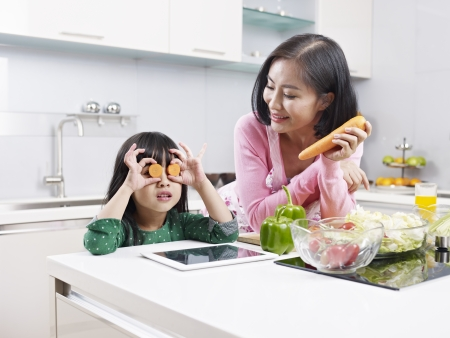 asian mother and daughter having fun in kitchen  Imagens