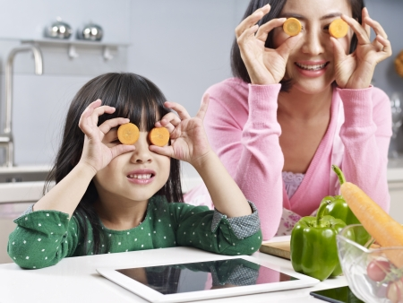 asian mother and daughter having fun in kitchen  Stock Photo
