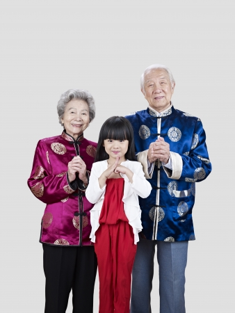 three generations: portrait of a senior chinese couple and their granddaughter  Stock Photo