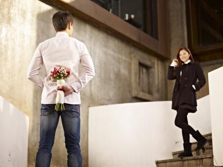 アジアの若い男が彼のガール フレンドの背中の後ろに花を持つの手順で待っています。