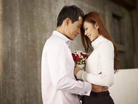 花と幸せなアジアの若い恋人の肖像画