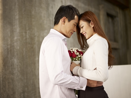 lovers embracing: portrait of happy asian young lovers with flowers