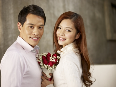 portrait of happy asian young lovers smiling with flowers  Stock Photo
