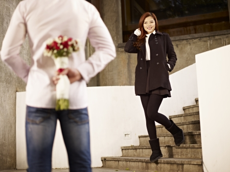 asian young man waiting by the steps with flowers behind back for his girlfriend