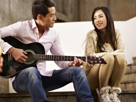 cantando: j�venes amantes asi�tico sentado en los escalones a tocar la guitarra y el canto